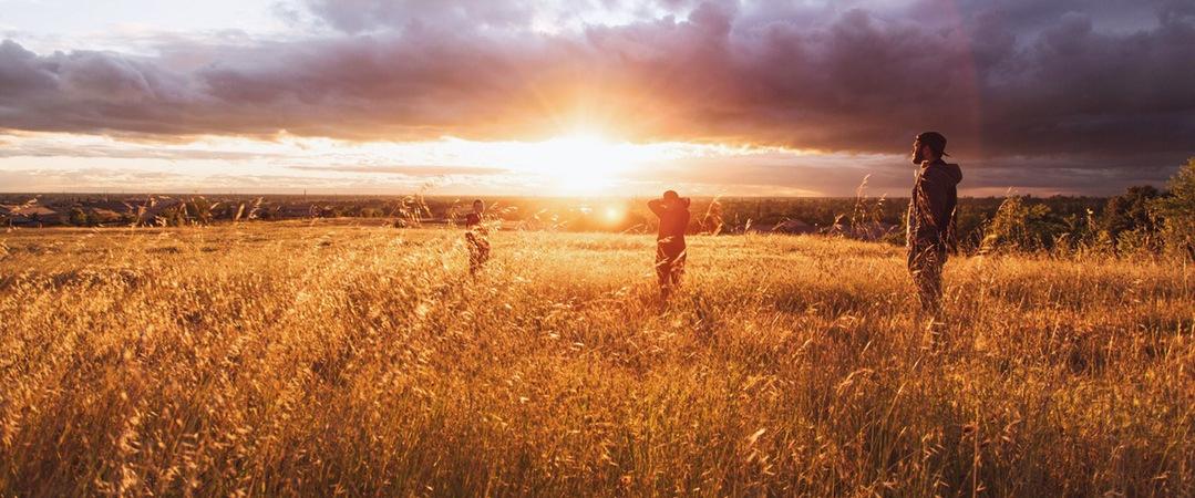 Familia contemplando puesta de sol desde un prado