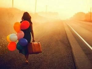 Psicoterapia: Persona con globos y maleta caminando junto a carretera