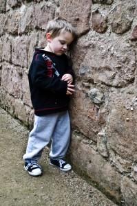 Infantil: Niño solo apoyado en la pared