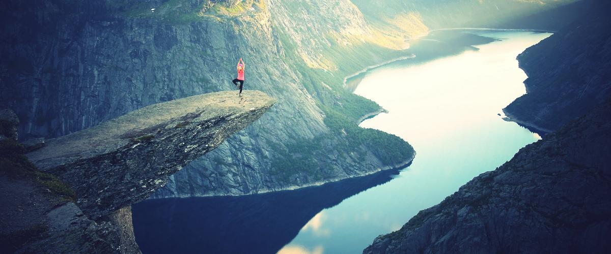 Persona haciendo yoga en un risco sobre un río entre montañas