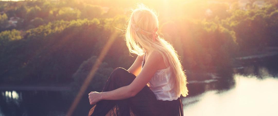 Mujer contemplando una puesta de sol junto a un lago