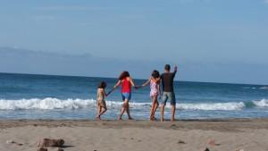 Psicoterapia: Familia de pie junto a la orilla mirando al mar